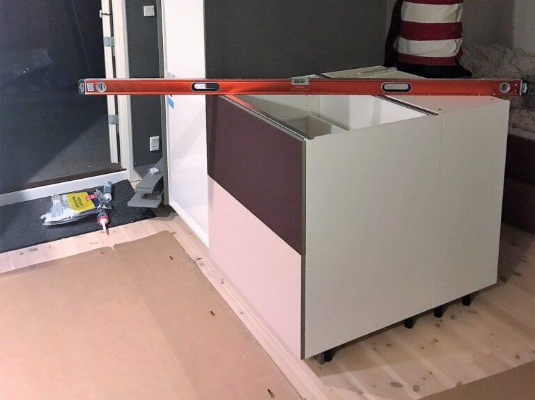 Integreret køkken og garderobe med linoleums fronter i farverne burgundy og powder