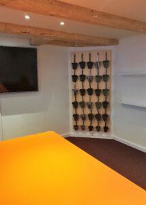 Billede af nyt mødelokale i orange med plantevæg og tv på på væggen