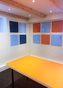 Ny indretning i mødelokale med tavler på væggen og orange bord